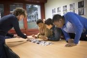 De gauche à droite, Ibrahima, Rayan, Hadama accompagné par Antoine Boureau en séance de lecture d'image devant des tirages de lecture imprimés en 10x15
